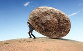 Homme d'affaires, rouler une pierre géante — Photo