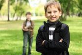 Chico con un amigo en el parque verde — Foto de Stock
