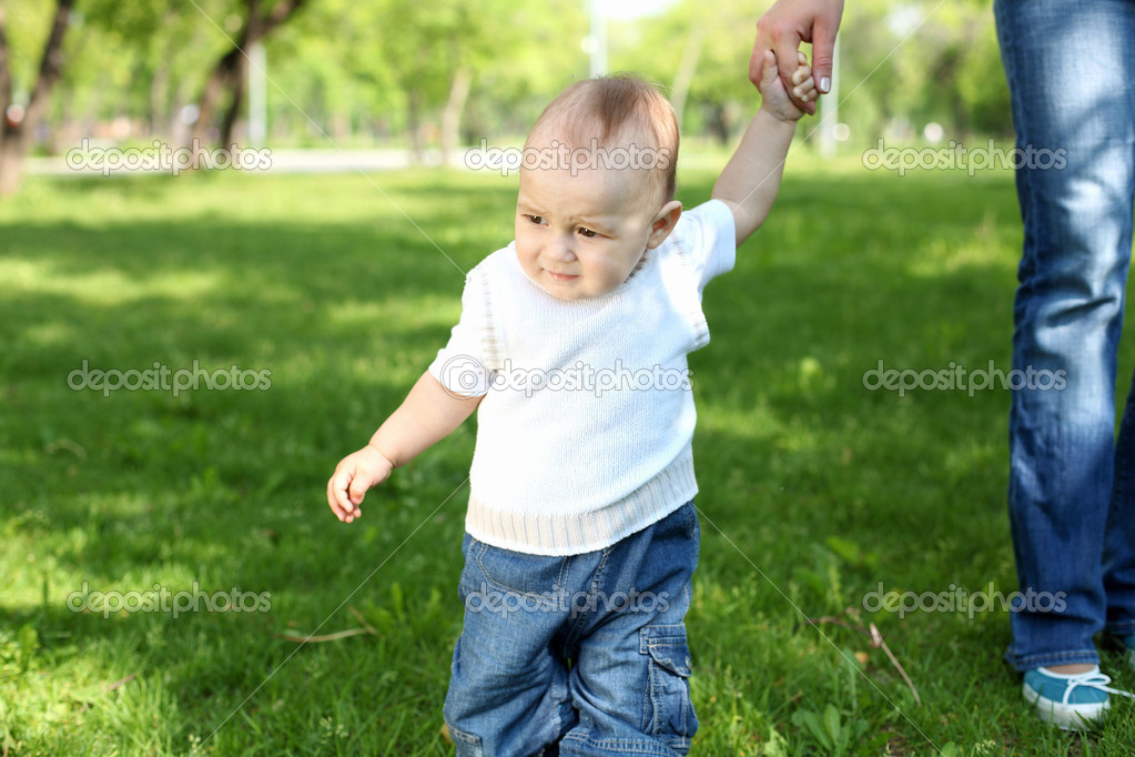 Portrait of a baby boy holding mother's hand in the park — Stock Photo #6853340