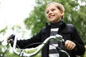 男孩骑着自行车在绿色公园 — 图库照片
