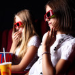 Two young girls watching in cinema — Stock Photo #6924450