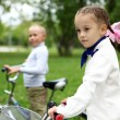 Girl on a bicycle in the green park — Stock Photo