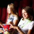 Two young girls watching in cinema — Stock Photo #6924771