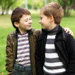 Boy with a friend in the green park - Stock Photo