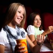 Two young girls watching in cinema — Stock Photo #6924793