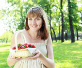 Young woman with strawberries outdoors — Stock Photo