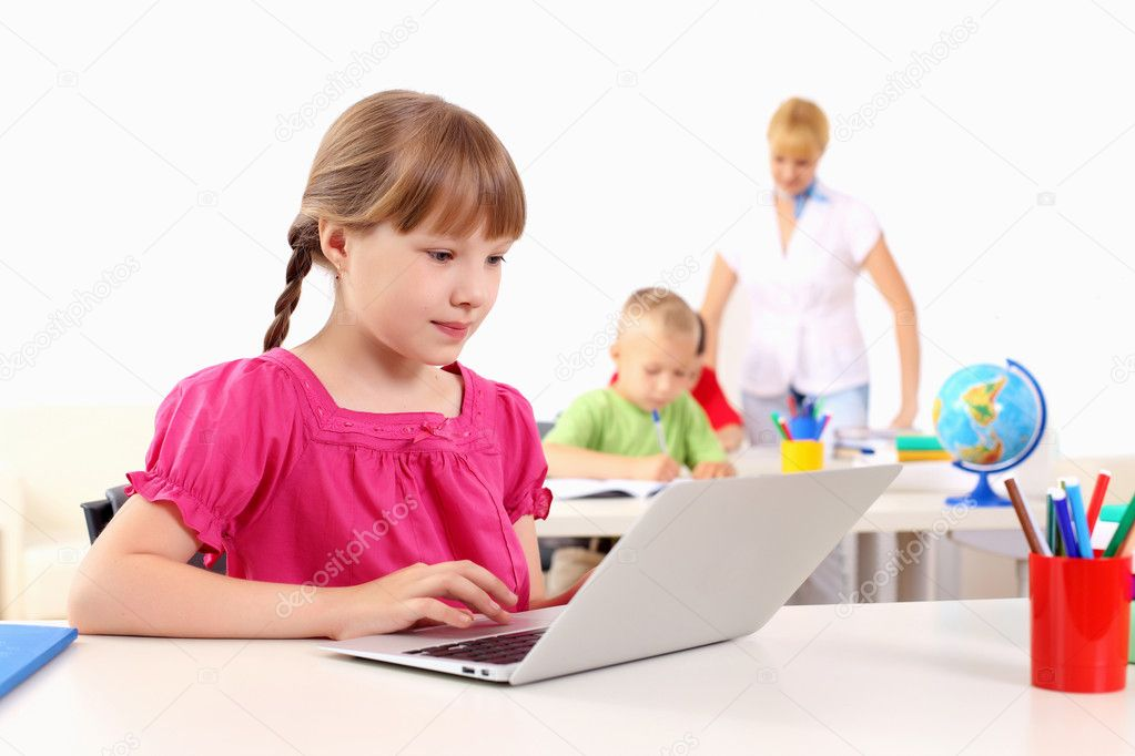 Portrait of a young girl working on laptop at school at the desk.  Stock Photo #6924528