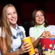 Two young girls watching in cinema — Stockfoto
