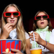 Two young girls watching in cinema — Stock Photo #6931904