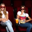 Two young girls watching in cinema — Stock Photo #6932094