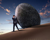 Businessman rolling a giant stone — Foto Stock