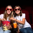 Two young girls watching in cinema — Stock Photo #6972806