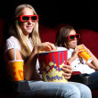 Two young girls watching in cinema — Stock Photo #6973018