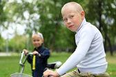 Junge auf einem Fahrrad in die grünen park — Stockfoto
