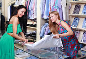Girl seller helps shoppers — Stock Photo