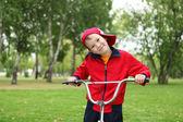 Jongen op een fiets in het groene park — Stockfoto