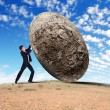 Royalty-Free Stock Photo: Businessman rolling a giant stone