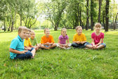 Group of children sitting together in the park — Stok fotoğraf