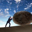 Businessman rolling a giant stone - Stock Photo