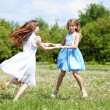 Two girls playing in the park - Stock Photo