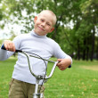 Boy on a bicycle in the green park - 图库照片