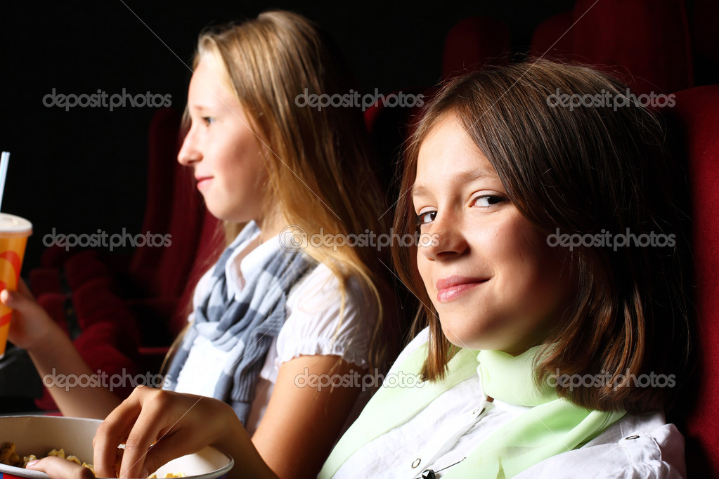 Two young girls watching movie in cinema — Stock Photo #7113792