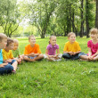 Group of children sitting together in the park — Stock Photo #7137057