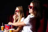 Two young girls watching in cinema — Stock fotografie