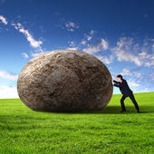 Businessman rolling a giant stone — Photo