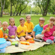 Group of children sitting together in the park — Stock Photo #7226185