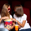 Two young girls watching in cinema — Stock fotografie