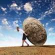 Businesswoman rolling a giant stone — Stock Photo