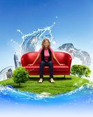 Junge frau sitzt auf dem sofa natur hintergrund — Stockfoto
