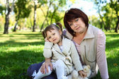 Grandmother with her little granddaghter in park — Stock Photo