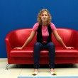 Young woman sitting on red sofa — Stock Photo #7461994