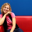Young woman sitting on red sofa — Stock Photo #7462039