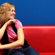 Young woman sitting on red sofa — Stock Photo #7462046