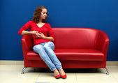 Ung kvinna sitter på röd soffa — Stockfoto