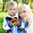 Young mother with her son in summer park - Stock Photo