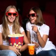 Two young girls watching in cinema — 图库照片