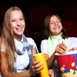 Two young girls watching in cinema — Foto de Stock