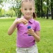 Little girl in the park blowing bubbles - Stockfoto