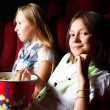 Two young girls watching in cinema — Stok fotoğraf