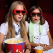 Two young girls watching in cinema — Stock Photo #7788302