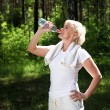 Elderly woman after exercising in the forest - Stock Photo