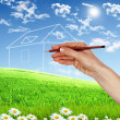 House from white clouds against blue sky - Stock Photo