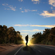 Man walking away at dawn along road — Foto de Stock