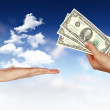 Human hands holding money against blue sky - Stock Photo
