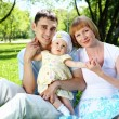 Young family together in the park — Stock Photo #7789729