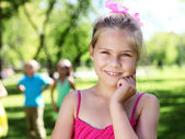 Little girl in summer park with friends — Стоковое фото